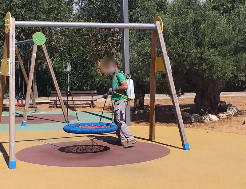 Un técnico municipal desinfecta los juegos infantiles