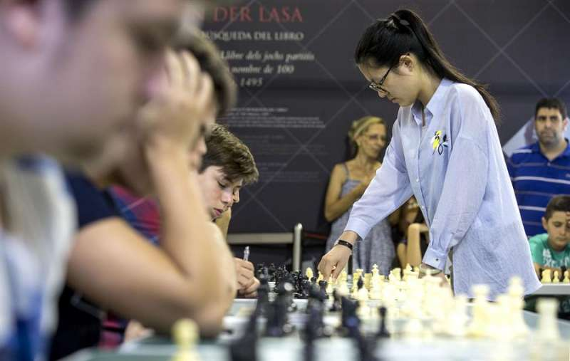 La campeona mundial de ajedrez, la china Yifan Hou durante la disputa de la partida simultánea contra quince jugadores de todas la edades. EFE/Manuel Bruque