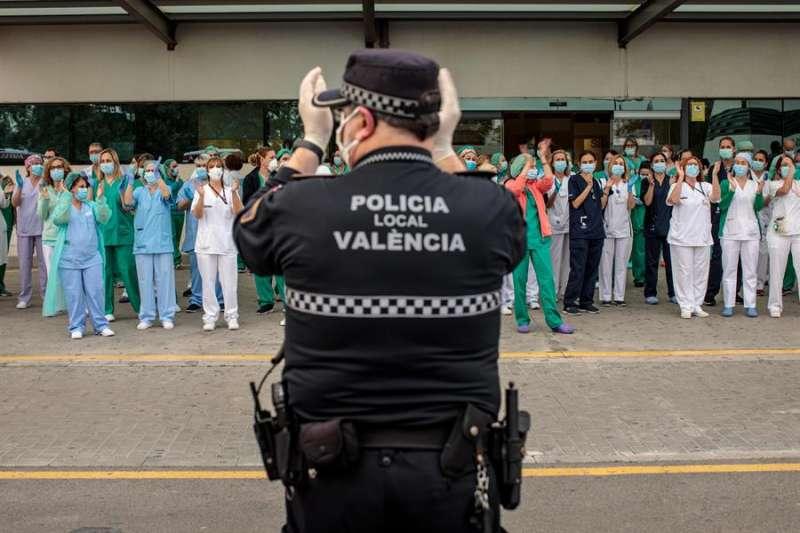 Un policía local y sanitarios del Hospital La Fe de Valencia, durante el aplauso diario en apoyo a todo el personal. EFE