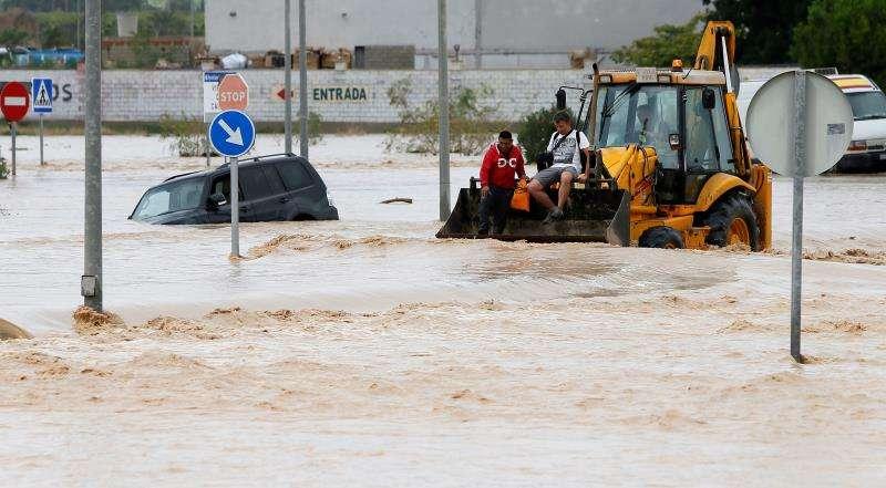 Dos ocupantes de un vehículo son rescatados con una pala mecánica, mientras la carretera permanece inundada por la gota fría, en una imagen de estos días. EFE/Manuel Lorenzo