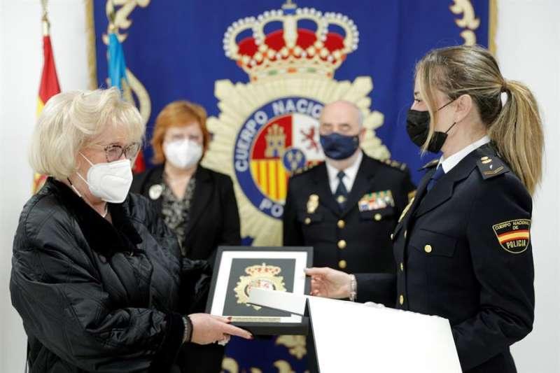 Una agente de la Policía Nacional entrega una placa a Maruja Tatay. EFE