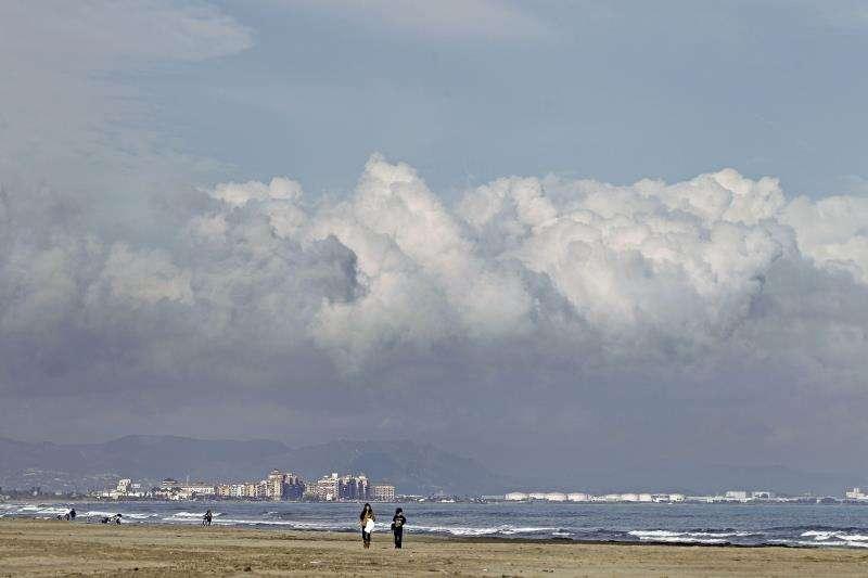 Una pareja pasea por la orilla de la playa de Las Arenas de València en un día de nubes y claros. EFE/Archivo