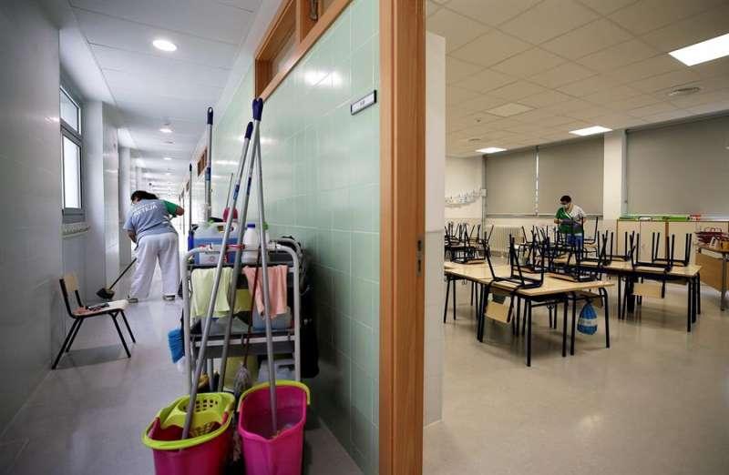 Dos trabajadoras del servicio de limpieza desinfectan los pasillos y sillas y pupitres de una clase de infantil. EFE