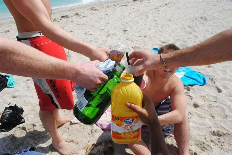 Varias personas brindan con bebidas alcohólicas en una playa. EFE/Antoni Belchi