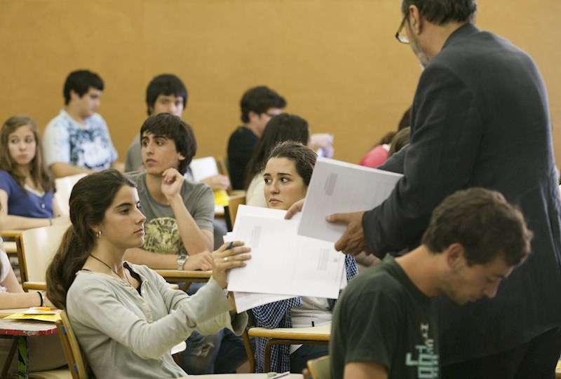 Un profesor reparte exámenes a sus alumnos. EFE/Archivo