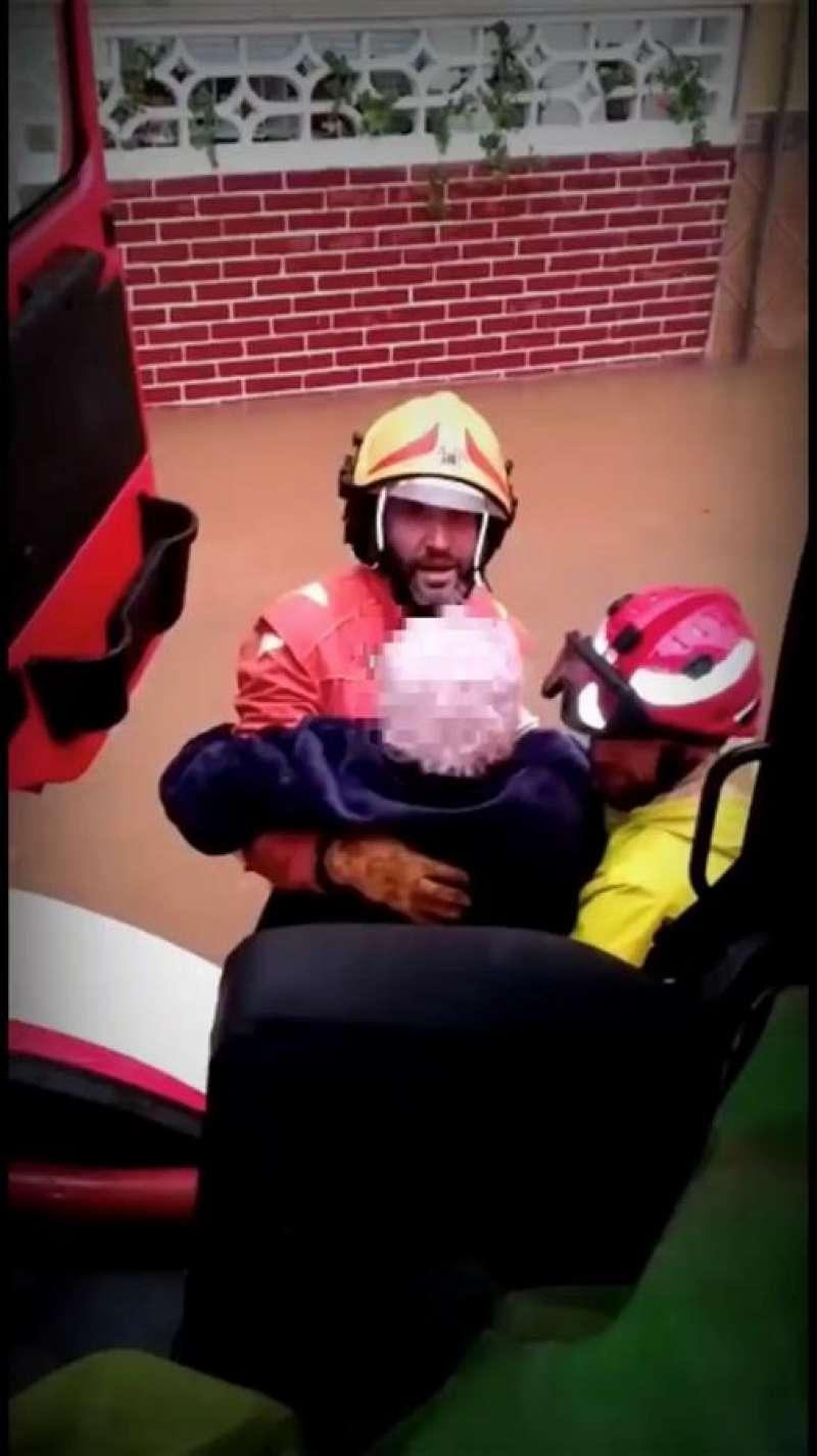 Momento en el que los bomberos rescatan a la mujer. EFE