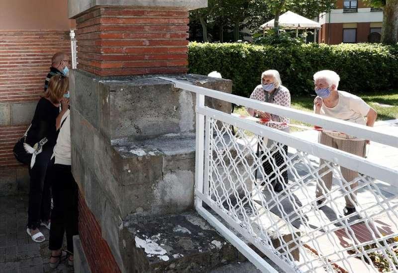 Unas personas conversan a distancia con dos internas de una residencia. EFE