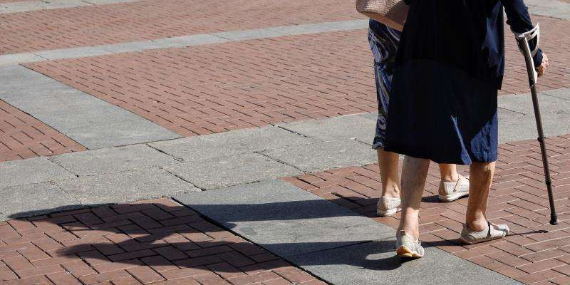 Dos personas mayores pasean juntas, una de ellas ayudada de una muleta. EFE/Archivo