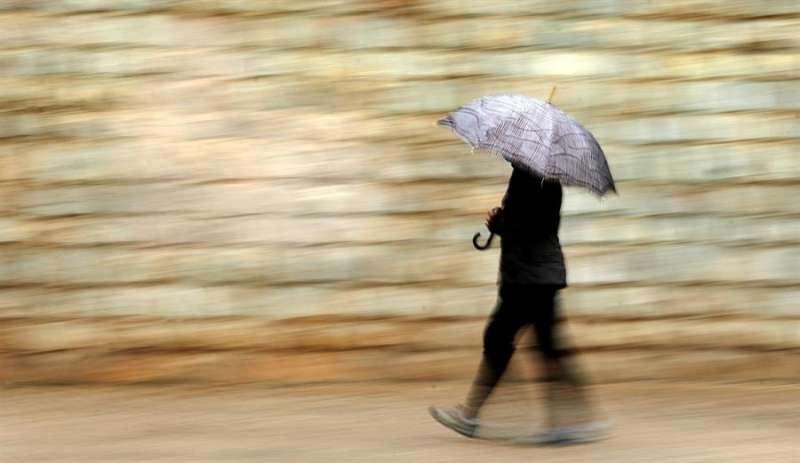 Una persona se protege de la lluvia con paraguas este jueves en Val�ncia. EFE