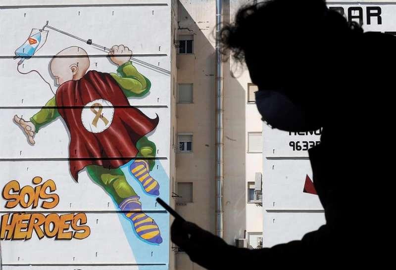 Imagen de archivo de una persona consultando el móvil en València frente a una pintada junto a La Fe. EFE