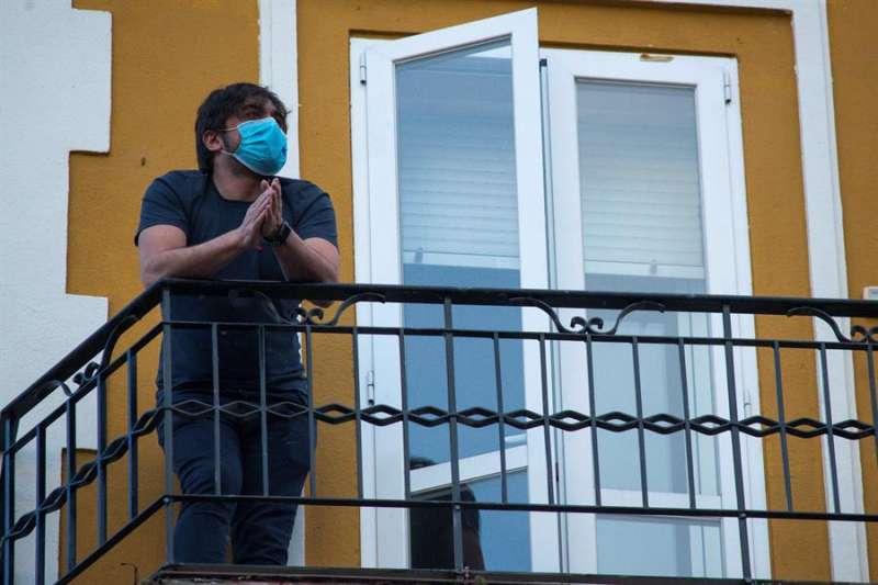 Una persona con mascarilla se asoma al balcón de su casa. EFE/Archivo