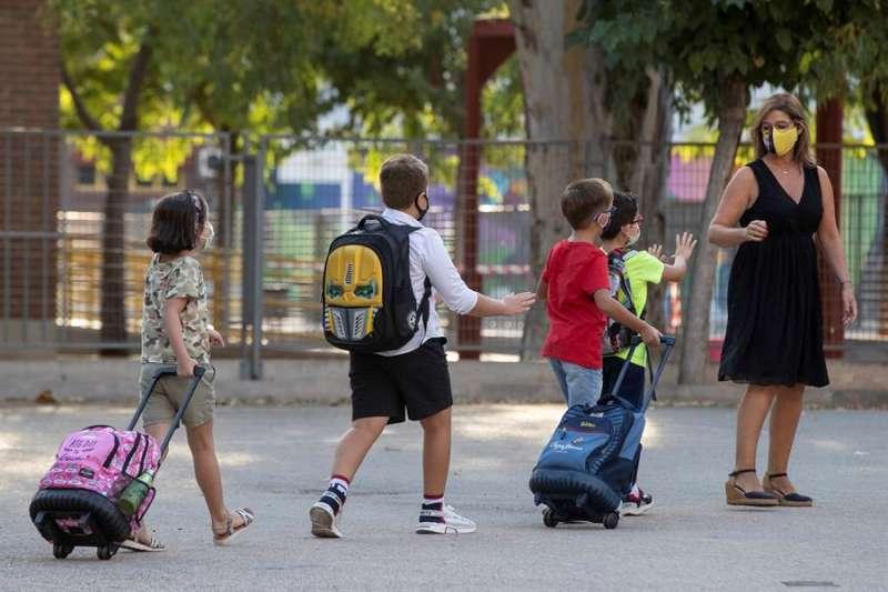 Una maestra indica a varios niños que guarden la distancia de seguridad. EFE/Archivo