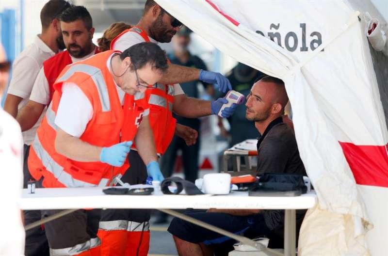 Miembros de la Cruz Roja atienden a inmigrantes de una patera detectada en las costas alicantinas. EFE/Manuel Lorenzo/Archivo