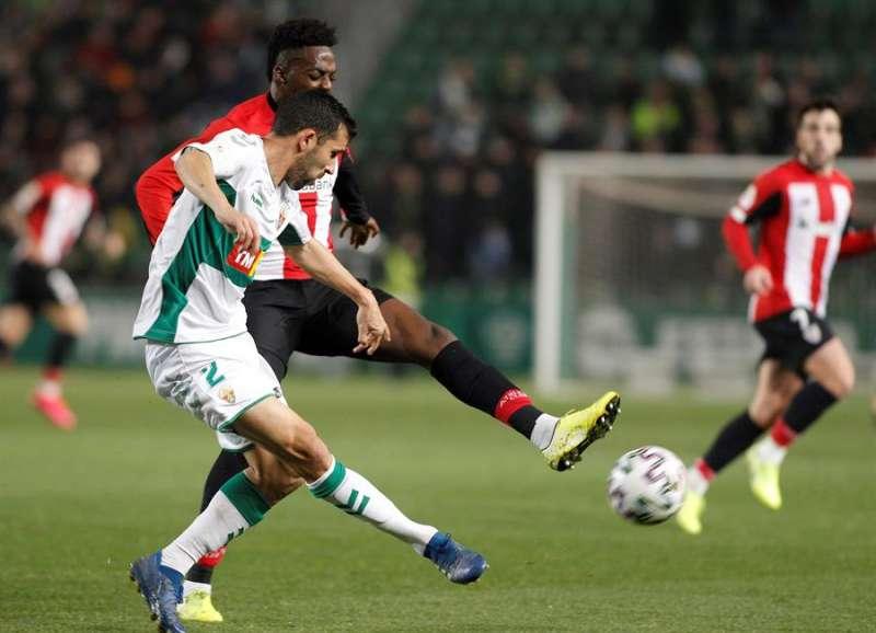 El delantero del Athletic Club de Bilbao Iñaki Williams (detrás) pelea un balón con el lateral derecho del Elche CF Sergio Blázquez,