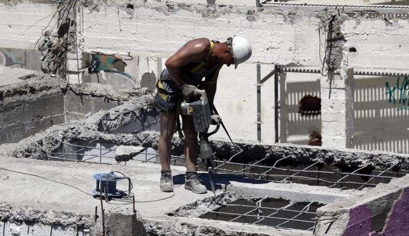Un trabajador de la construcción trabajando en un derribo a pleno sol. EFE/Archivo