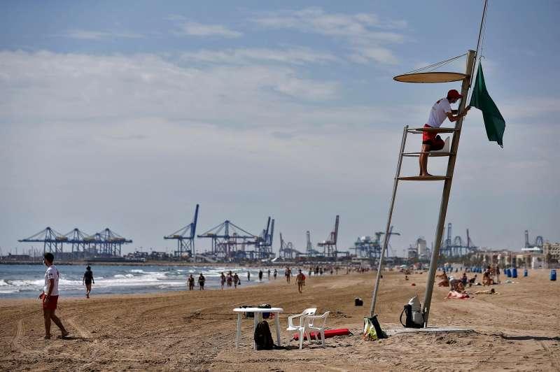 Un socorrista de la Cruz Roja iza la bandera verde en la playa de La Malvarrosa de València.