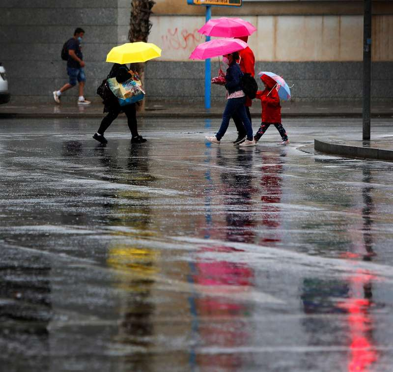 Transeúntes en Alicante bajo la lluvia en una imagen de archivo. EFE/Manuel Lorenzo/Archivo