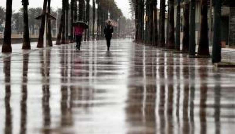 En la imagen, dos mujeres pasean bajo la lluvia por el paseo marítimo de Alboraia en octubre pasado. EFE/Manuel Bruque/Archivo