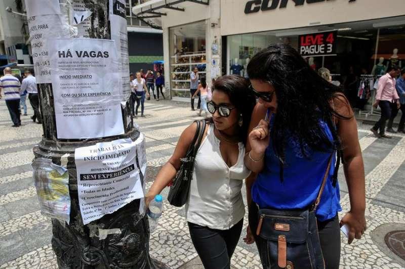 Dos mujeres observan algunas ofertas de trabajo publicadas en un poste en el centro de Sao Paulo (Brasil). EFE
