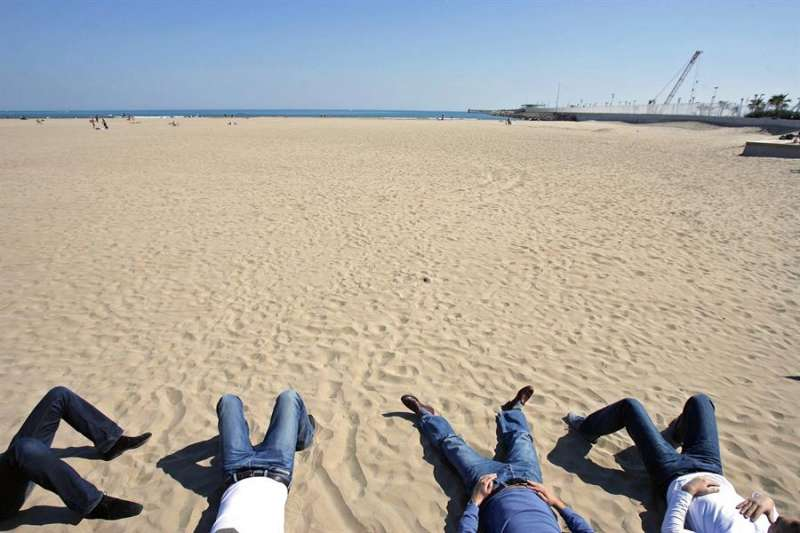 Unos jóvenes toman el sol en la playa de Las Arenas de València, fuera de temporada. EFE/Manuel Bruque/Archivo