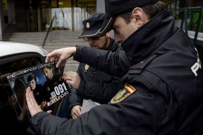 Dos agentes colocan una pegatina contra la violencia de género. EFE