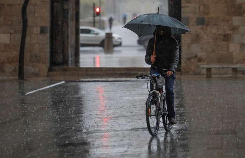 Un ciclista se protege de la lluvia. EFE/Ana Escobar/Archivo