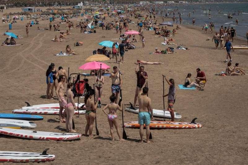 Miles de personas, muchos de ellos madrileños, disfrutan en la playa de València durante el primer día de la ?nueva normalidad? tras el fin del estado de alarma. EFE/Biel Aliño