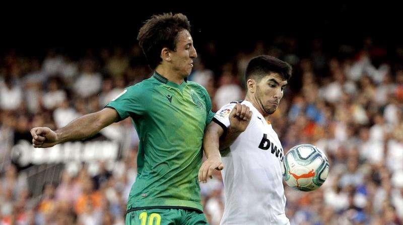 Carlos Soler y Mikel Oyarzabal durante el partido correspondiente a la primera jornada de LaLiga Santander. EFE/Manuel Bruque