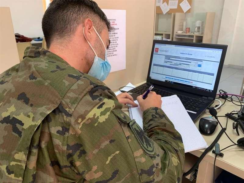 En un cubículo acristalado, con el sitio justo para un ordenador y un teléfono, Iván encara su segundo día como rastreador. EFE/María Traspaderne