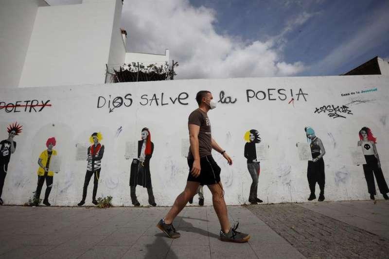 Un joven protegido con mascarilla pasa junto a unos graffiti. EFE/Archivo