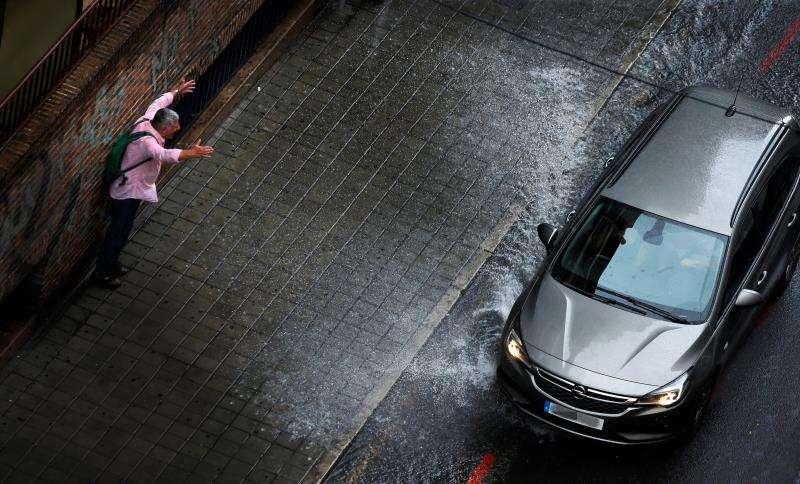Un hombre se queja ante el agua lanzada por un vehículo a su paso por una calle de Alicante tras la lluvia caída este medio día en la ciudad. EFE