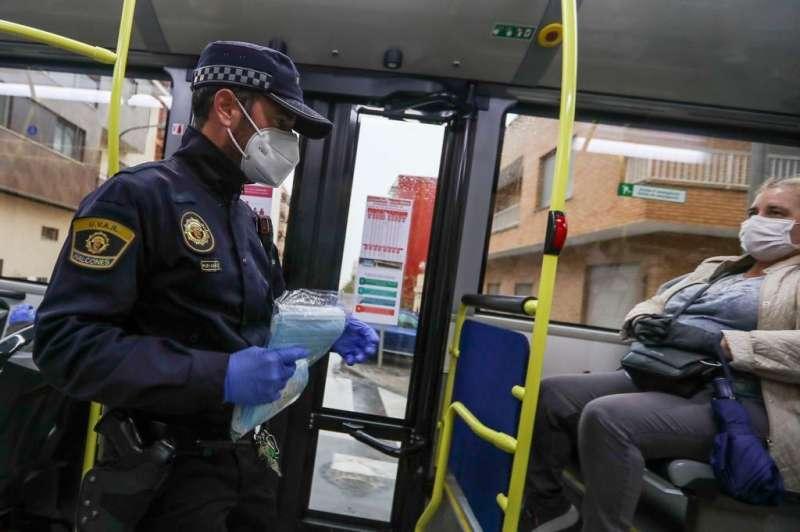 Un policía reparte mascarillas en el transporte. EPDA