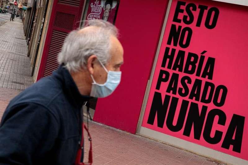 Un hombre con mascarilla camina por la calle durante la quinta jornada de confinamiento tras decretarse el estado de alarma. EFE/Biel Aliño