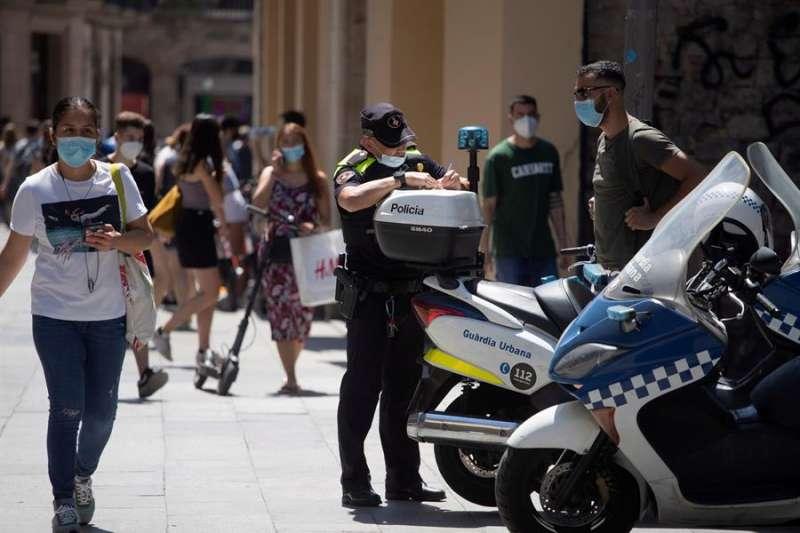 Un policía multa a un ciclista por una infracción cometida y le advierte también de la obligatoriedad de llevar mascarilla cuando se viaja, hoy en el centro de Barcelona. EFE/Marta Pérez