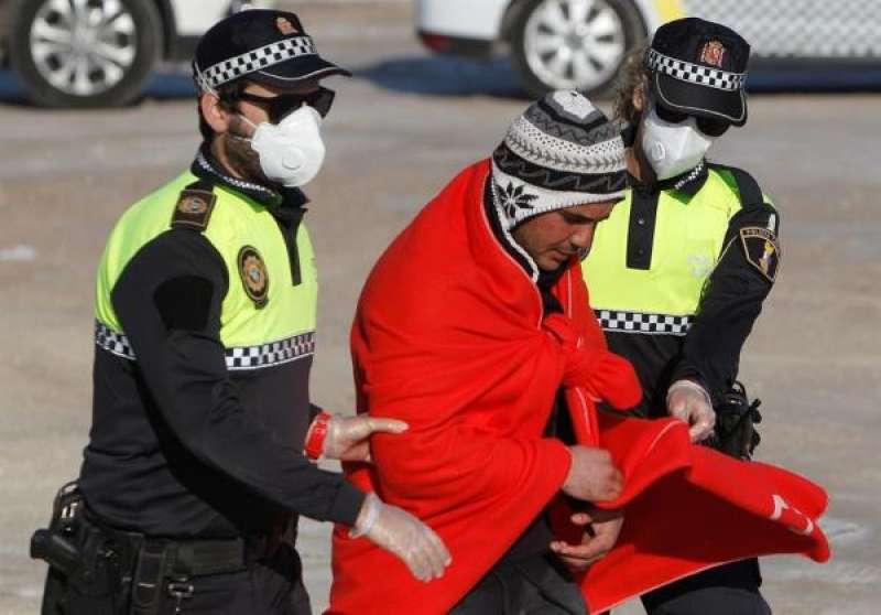 Dos policías acompañan a un inmigrante llegado a la costa de Alicante, en una imagen de archivo. EFE/MORELL./ EPDA