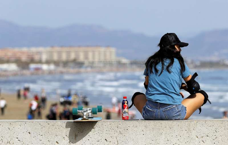 Una joven observa la playa de Las Arenas desde el espigón de la Marina del Puerto de València.