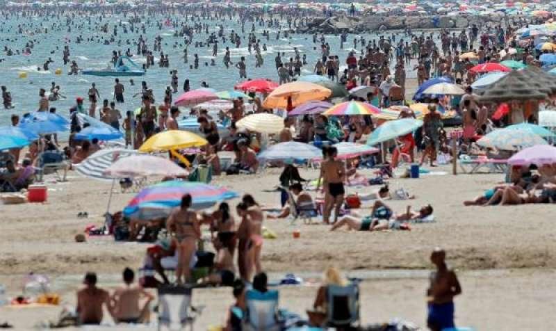 Un gran número de personas se ha acercado a la playa de la Patacona para disfrutar del buen tiempo veraniego y mitigar las altas temperaturas que se viven este fin de semana. EFE/Kai Försterling