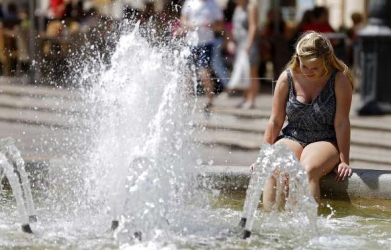 Un mujer dentro de una fuente por el elevado calor. EPDA