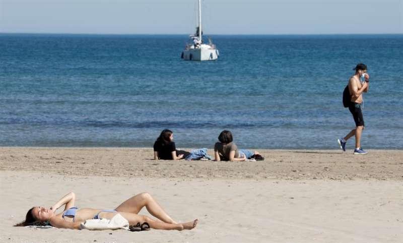 Varias personas toman hoy el sol en una playa valenciana. EFE