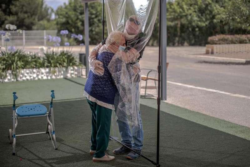 Una interna en una residencia de mayores abraza a su hijo con medidas de seguridad por el coronavirus. EFE/Biel Aliño