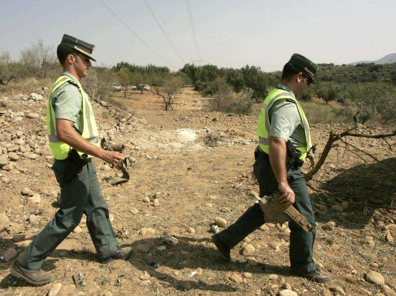 Agentes de la Guardia Civil retiran en un huerto de olivos del término municipal de Les Coves de Vinromà (Castellón) trozos de la autocaravana que un comando ETA explotó. EFE/Archivo