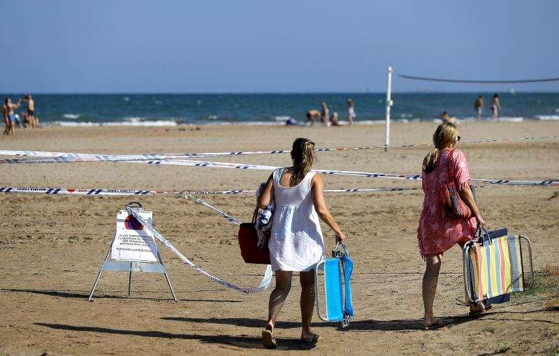 Dos bañistas pasan junto a una prohibición de bañarse. EFE/Archivo
