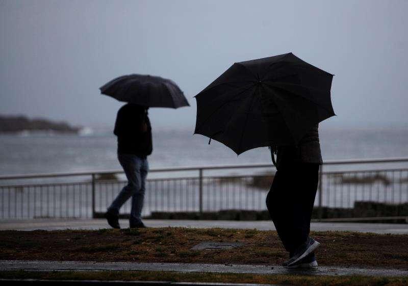 Dos personas caminan bajo la lluvia. EFE/Archivo