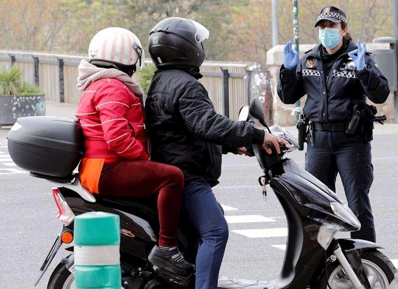 Una agente de la Policía Local de Valencia pregunta a dos personas que circulan en moto por el motivo para desplazarse. EFE