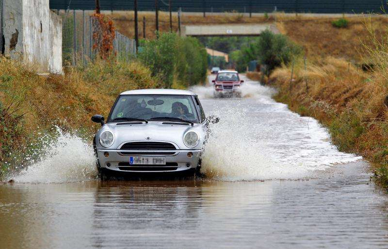 Varios vehículos circulan por un camino inundado por una intensa tormenta en la provincia de Castellón. EFE