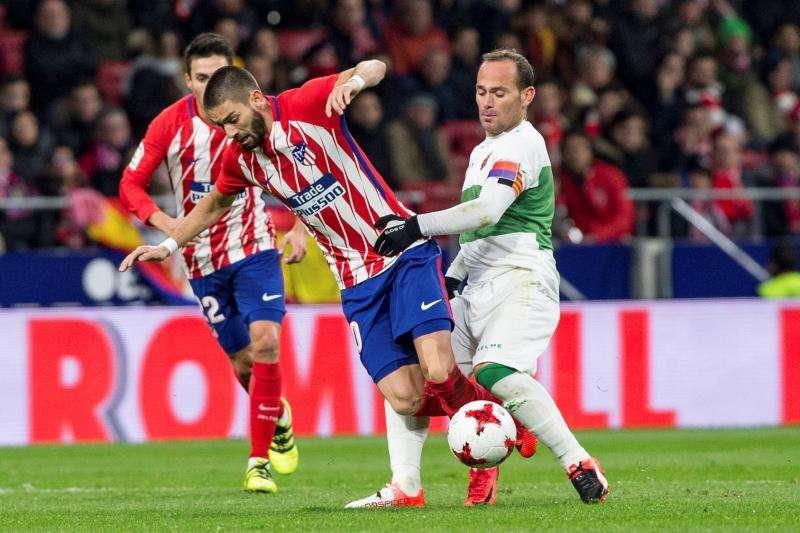 El centrocampista belga del Atlético de Madrid, Yannick Ferreira Carrasco (c), intenta llevarse el balón ante la entrada del delantero del Elche, Juan Francisco Martínez