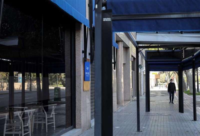 Una persona con mascarilla pasa por uno de los bares y restaurantes que permanecen cerrados en València, tras el estado de alarma por el coronavirus, en una imagen de esta semana. EFE/Ana Escobar
