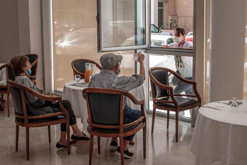 Una persona conversa con sus padres a través de una ventana habilitada en la residencia de mayores Ballesol Patacona. EFE