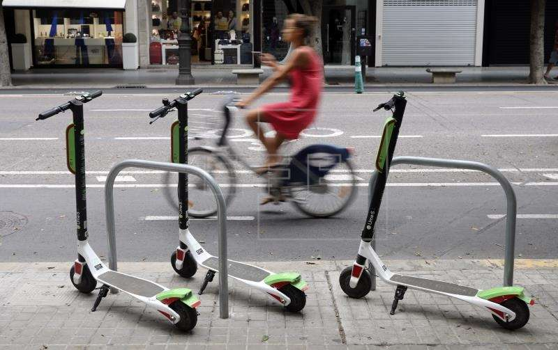 La nueva ordenanza de Movilidad estará lista antes del final de septiembre. Vista general de un aparcamiento de bicicletas en el centro de la ciudad con tres patinetes de la empresa Lime. EFE