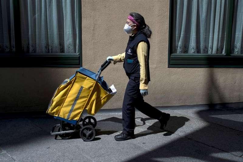 Una trabajadora de Correos camina por una calle. EFE